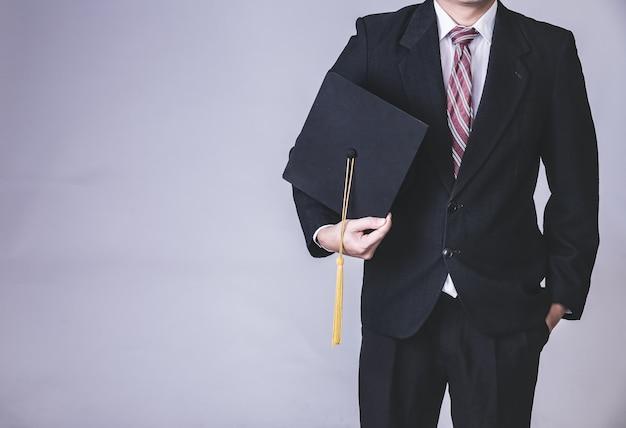 Biznesmen trzyma kapelusz ukończenia szkoły Premium Zdjęcia