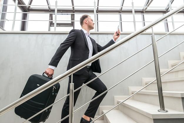 Biznesmen Trzymając Walizkę Na Schodach W Nowoczesnym Budynku Premium Zdjęcia