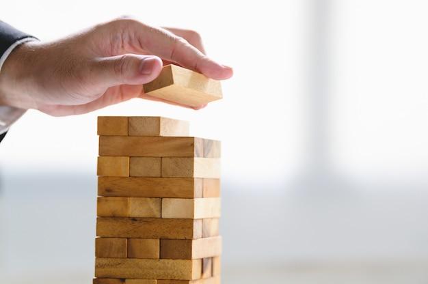 Biznesmen układania bloku drewna i układania jak wieża ręcznie. Premium Zdjęcia