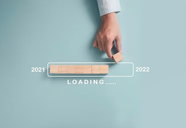 Biznesmen Umieszcza Drewniane Kostki Blokowe W Celu Przygotowania Postępów Przesyłania W Latach 2021 Do 2022, Koncepcja Biznesowa Wesołych świąt I Szczęśliwego Nowego Roku. Premium Zdjęcia