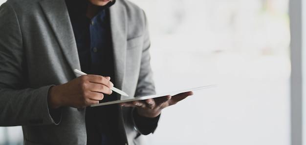 Biznesmen Używa Cyfrową Pastylkę Podczas Gdy Pracujący Nad Jego Projektem Premium Zdjęcia