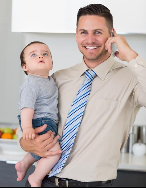Biznesmen Używa Telefon Komórkowego Podczas Gdy Niosący Dziecka W Domu Premium Zdjęcia