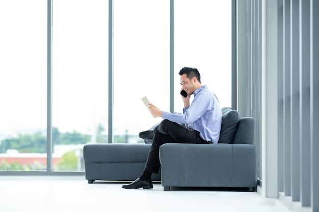 Biznesmen używa wiszącą ozdobę w biurze. Premium Zdjęcia