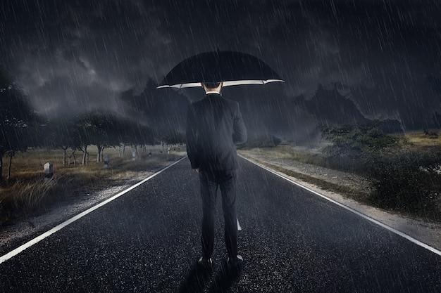 Biznesmen w deszczu z parasolową pozycją Premium Zdjęcia