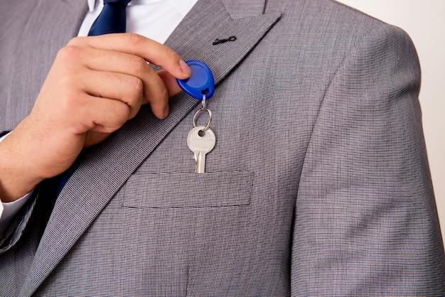 Biznesmen w nieruchomości pojęciu z domowym kluczem Premium Zdjęcia