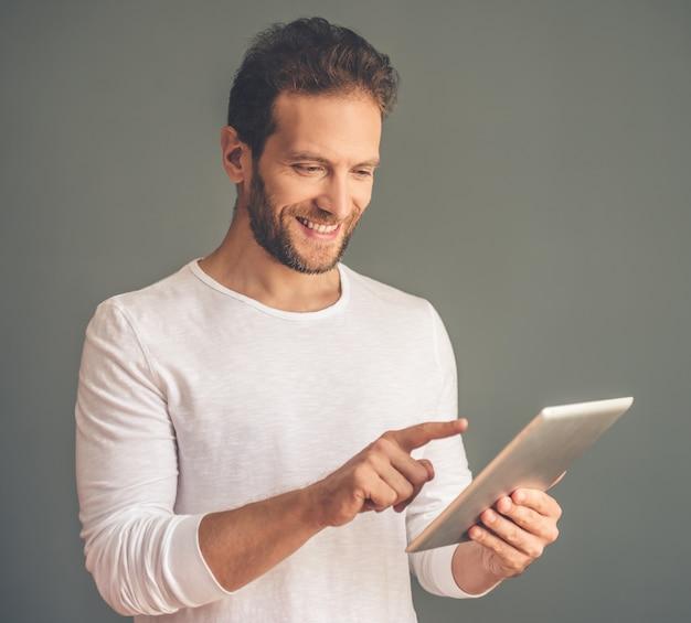 Biznesmen w przypadkowych ubraniach używa cyfrową pastylkę Premium Zdjęcia
