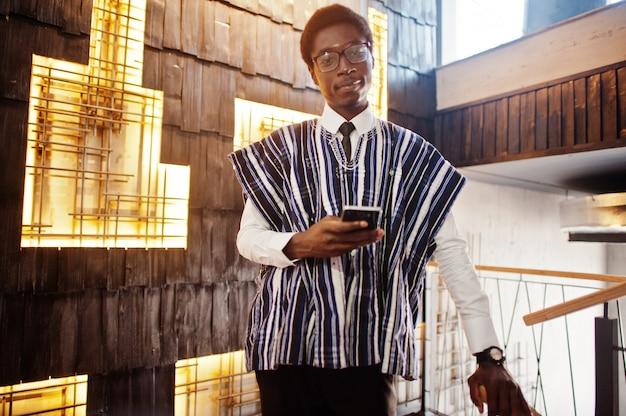 Biznesmen W Tradycyjnych Ubraniach I Szkłach Z Telefonem Komórkowym Gotowym Pozującym Przy Nowożytnym Budynkiem Salowym Premium Zdjęcia