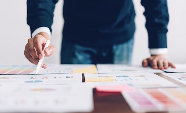 Biznesmen wskazując cyfrowe pióra i pracy na stole i dokumentów finansowych w biurze Premium Zdjęcia