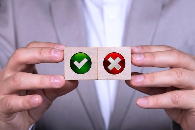 Biznesmen Wybiera Jedną Z Dwóch Kostek Z Ikonami Tak I Nie. Premium Zdjęcia