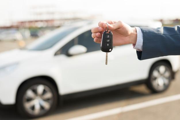 Biznesmen z kluczami przed samochodem Darmowe Zdjęcia