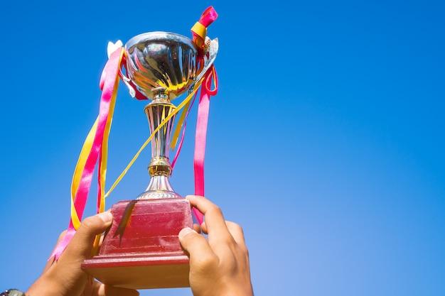 Biznesmena mienia nagrody trofeum złoto z tasiemkowym przedstawienia zwycięstwem dla najlepszego sukcesu osiągnięcia i nagrody biznes jako zwycięzca rywalizacja z niebieskim niebem Premium Zdjęcia