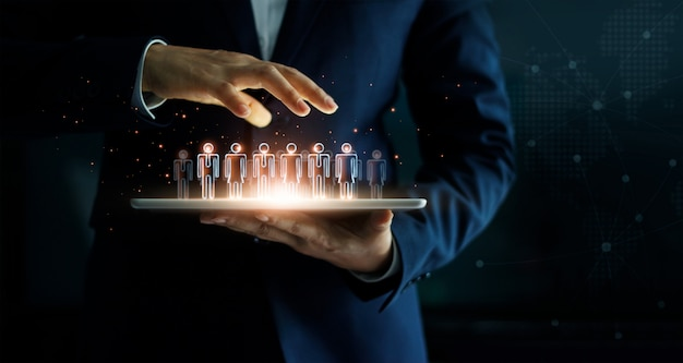 Biznesmena mienia pastylka i zarządzanie grupa ludzi w jego ręce. Premium Zdjęcia