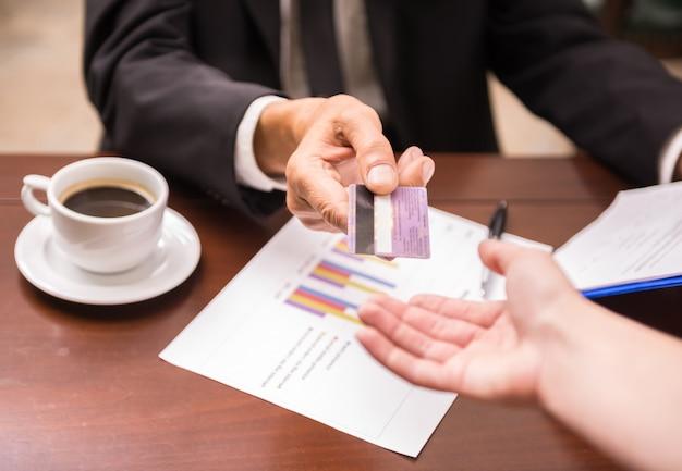 Biznesmena Obsiadanie W Kawiarni I Dawać Kredytowej Karcie Kelner Premium Zdjęcia