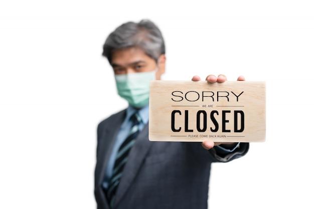 Biznesmeni Noszą Maski Medyczne Na Białym Tle I Przepraszam, że Jesteśmy Zamknięci Znak Premium Zdjęcia