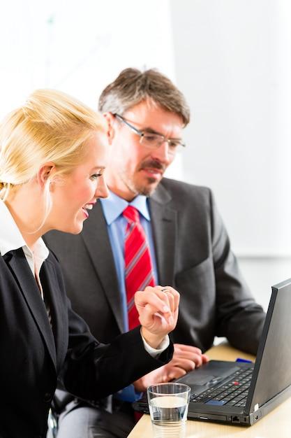 Biznesmeni patrzeje laptop w konsultacji Premium Zdjęcia