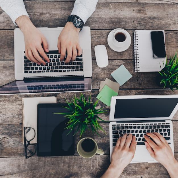 Biznesmeni pracujący na swoich komputerach. widok z góry Premium Zdjęcia