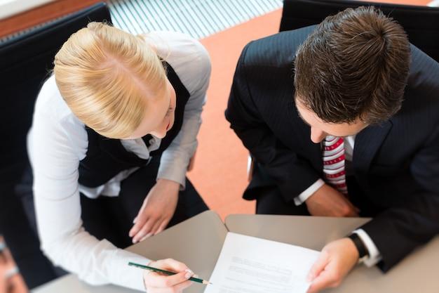 Biznesmeni siedzą przy biurku Premium Zdjęcia