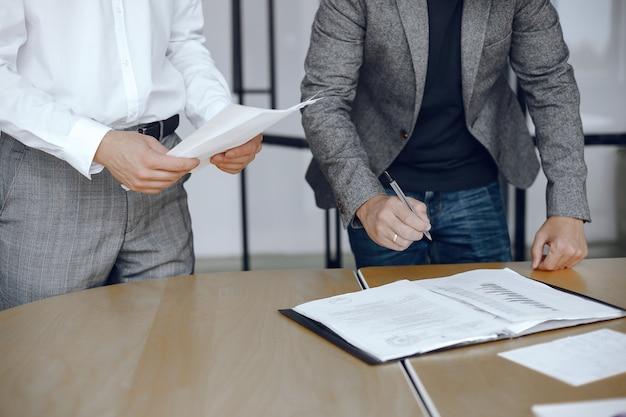 Biznesmeni Siedzący Przy Biurku Prawników. Osoby Podpisujące Ważne Dokumenty. Darmowe Zdjęcia