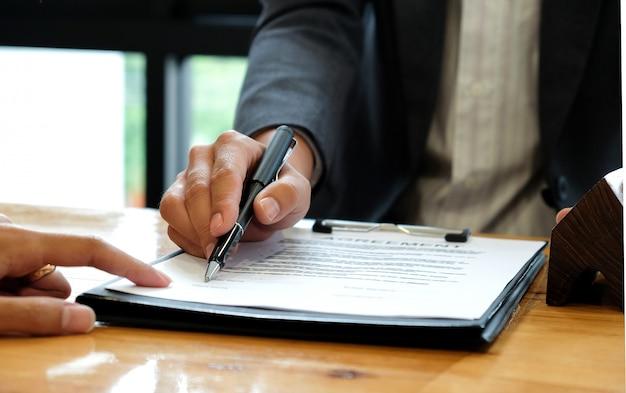 Biznesmeni sprzedający dom wskazując na podpisanie umowy sprzedaży w biurze. Premium Zdjęcia