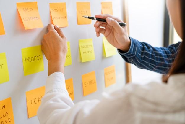Biznesmeni Układają Notatki Z Kolegami I Przeprowadzają Burze Mózgów Na Temat Priorytetów Pracy Kolegi W Nowoczesnej Przestrzeni Coworkingowej. Premium Zdjęcia