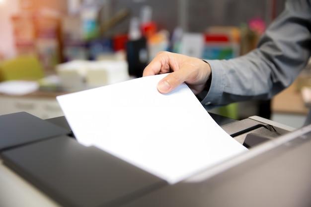 Biznesmeni umieszczają papiery na kserokopiarkach. Premium Zdjęcia