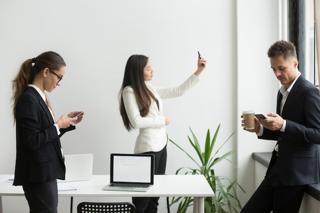 Biznesmeni używa smartphones texting, bierze selfie w biurze podczas przerwy Darmowe Zdjęcia