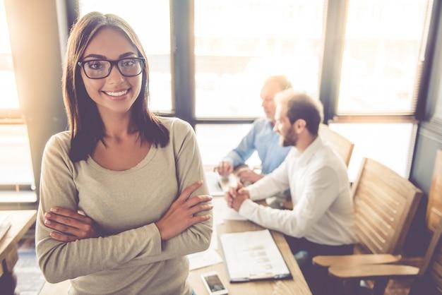 Biznesowa Dama W Eyeglasses Jest Przyglądającym Kamerą I Ono Uśmiecha Się Premium Zdjęcia