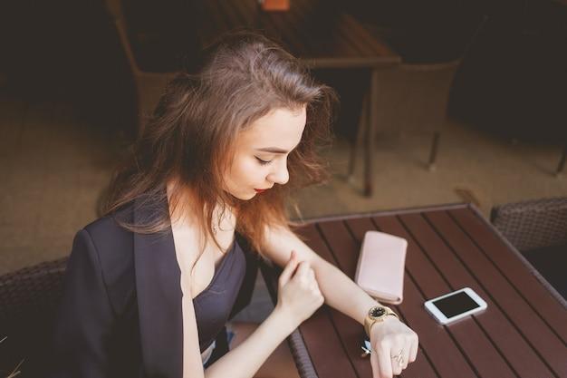 Biznesowa Kobieta Siedzi Samotnie Przy Restauracyjnym Stołem Podczas Gdy Patrzejący Zegar Premium Zdjęcia