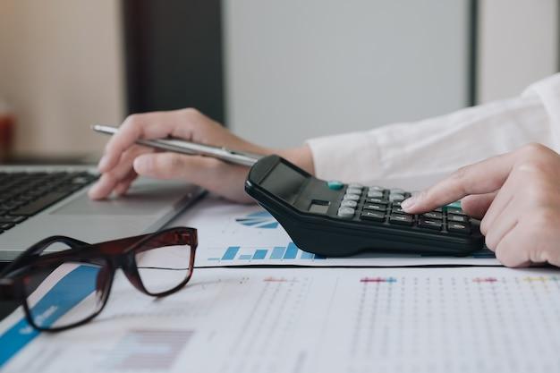 Biznesowa Kobieta Używa Kalkulatora I Laptopu Dla Robi Matematyka Finansowi Na Drewnianym Biurku W Biurze Premium Zdjęcia