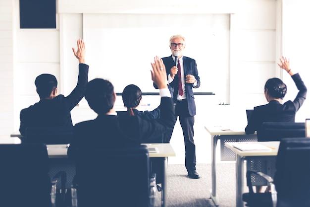 Biznesowa publiczność podnosząc rękę i mówiąc w szkoleniu o opinię w spotkaniu Premium Zdjęcia