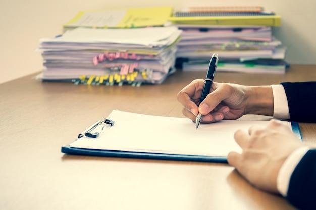 Biznesowa sukcesu ręki podpisywania kontrakta forma na drewnianym biurku w biurze. Premium Zdjęcia