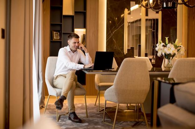 Biznesowego Mężczyzna Obsiadanie W Luksusowym Pokoju Przed Laptopem Premium Zdjęcia