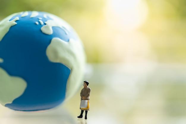 Biznesowej Kobiety Miniatury Postaci Ludzie Jest Ubranym Maskę Z Torebki Pozycją Z Mini światową Piłką Premium Zdjęcia