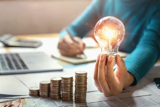 Biznesowej Kobiety Ręki Mienia Lightbulb Z Monet Stosem Na Biurku. Koncepcja Oszczędzania Energii I Pieniędzy Premium Zdjęcia
