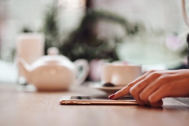Biznesowej Kobiety Ręki Używać Mądrze Telefon I Filiżankę Kawy. Premium Zdjęcia