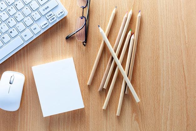 Biznesowi przedmioty klawiatura, mysz, ołówki, białego papieru notatka i szkła na drewnianym biurowym biurku dla biznesowego tła i projekta Premium Zdjęcia