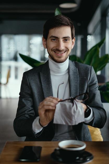 Biznesowy Mężczyzna Czyści Jego Szkła Z Filiżanką Kawy Darmowe Zdjęcia