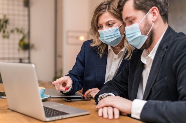 Biznesowy Mężczyzna I Kobieta Rozmawiają O Nowym Projekcie W Maskach Medycznych Darmowe Zdjęcia