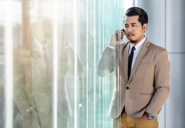 Biznesowy Mężczyzna Opowiada Z Telefonem Komórkowym W Biurze Premium Zdjęcia