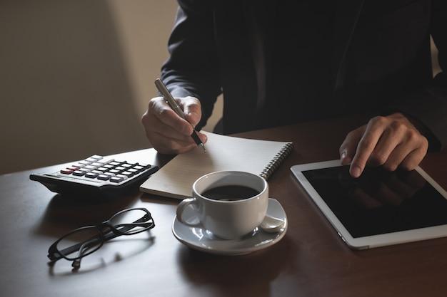 Biznesowy Mężczyzna Pracuje Na Cyfrowej Pastylce Na Drewno Stole Premium Zdjęcia