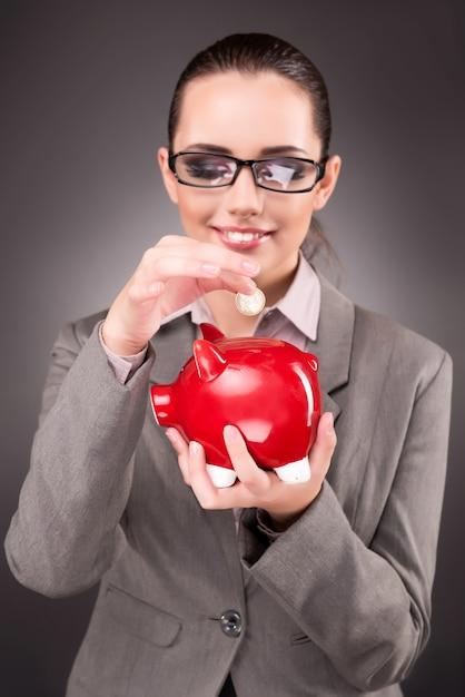 Biznesowy pojęcie z bizneswomanem i prosiątko bankiem Premium Zdjęcia