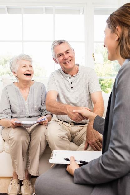 Bizneswoman opowiada z starszą parą w domu Premium Zdjęcia