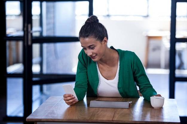 Bizneswoman Patrzeje Jej Telefon Komórkowego I Trzyma Kawę Premium Zdjęcia