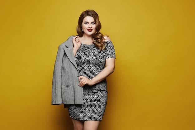 Bizneswoman Plus Size Z Jasnym Makijażem I Stylową Fryzurą W Sukience Z Geometrycznymi Wzorami Pozującymi Na żółto, Na Białym Tle Premium Zdjęcia