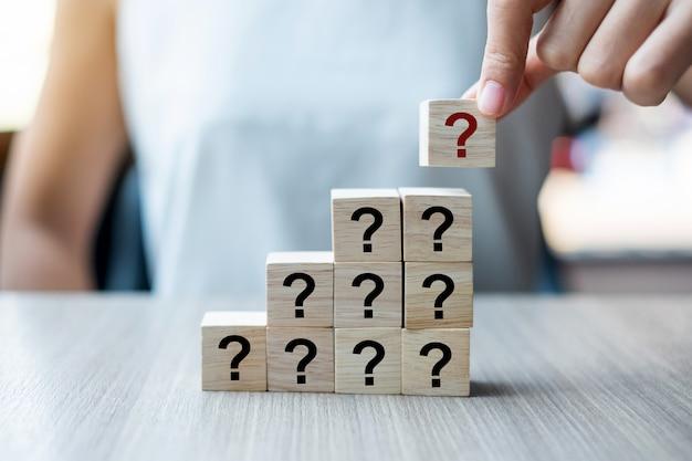 Bizneswoman ręka umieszcza pytania mark słowo (?) z drewnianym sześcianem Premium Zdjęcia