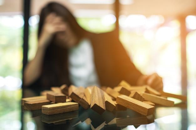 Bizneswoman Stresuje Się Podczas Gdy Mieć Problem Przy Pracą W Biurze Z Drewnianymi Blokami Tumble Wierza Gra Na Stole Premium Zdjęcia