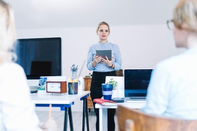 Bizneswoman trzyma cyfrową pastylkę? w ręce dając prezentację kolegom w biurze Darmowe Zdjęcia