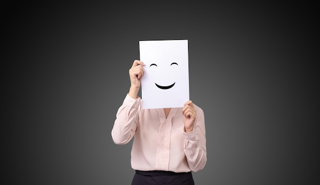 Bizneswoman trzyma kartę z rysować wyraz twarzy ilustracj emocj uczuć twarz na białym papierze Premium Zdjęcia