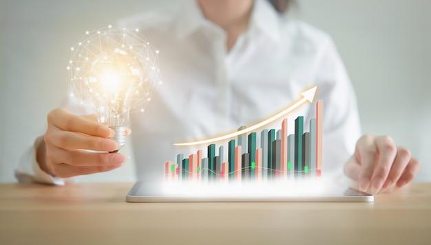 Bizneswoman trzyma żarówkę z innowacją i kreatywnością to klucze do sukcesu. Premium Zdjęcia