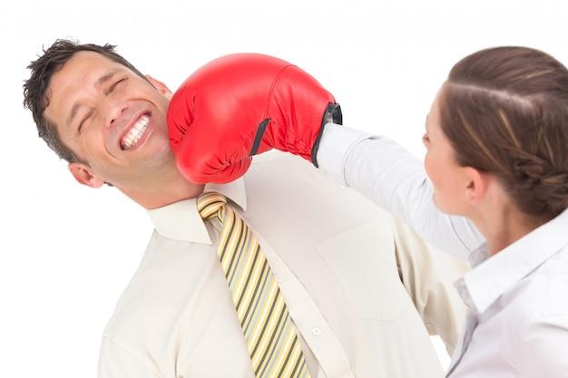 Bizneswoman Uderza Pięścią Biznesmena Z Bokserskimi Rękawiczkami Premium Zdjęcia